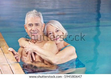 Happy couple senior people bathing in a swimming pool - stock photo