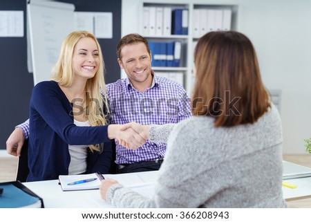Happy couple shaking hands with a female business broker or investment adviser as they attend a meeting in her office - stock photo