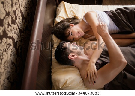Happy couple sharing moments in bed - stock photo