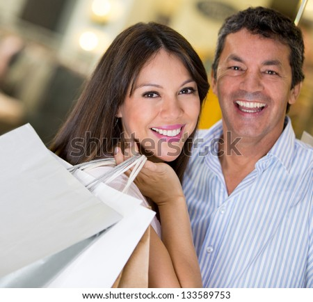 Happy couple shopping holding bags and smiling - stock photo