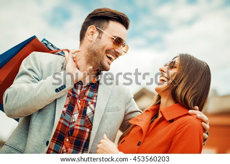 Happy couple shopping together in the city. - stock photo