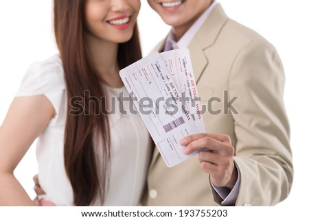 Happy couple showing airplane tickets - stock photo