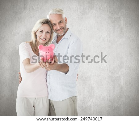 Happy couple showing their piggy bank against weathered surface - stock photo