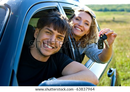Happy couple showingh the keys sitting in new car - stock photo