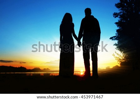 happy couple silhouette against a sunset romance - stock photo