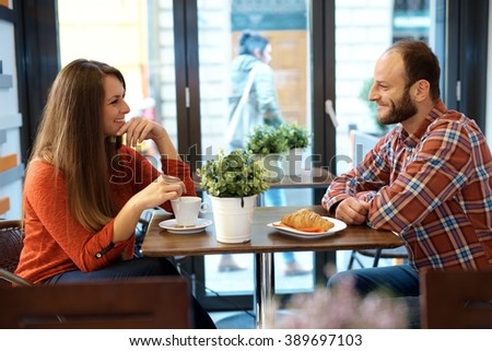 Happy couple sitting and chatting in cafe, drinking coffee, having croissant. - stock photo