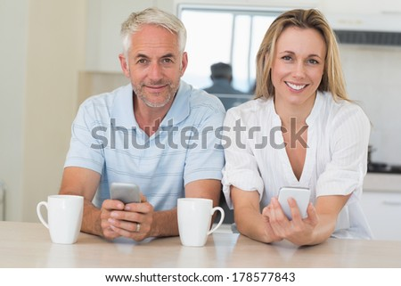 Happy couple sitting at the counter texting at home in the kitchen - stock photo