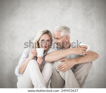 Happy couple sitting holding mugs against weathered surface - stock photo
