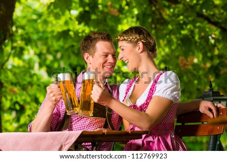 Happy Couple sitting in Beer garden in summer and enjoy a glass of beer and the sun - stock photo