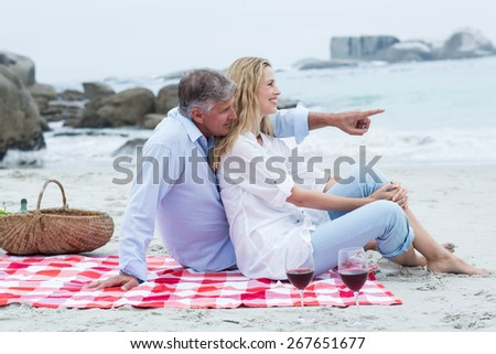 Happy couple sitting on a blanket and hugging each other at the beach - stock photo