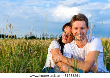 Happy couple sitting on a meadow or grainfield in summer embracing each other - stock photo