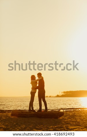 Happy couple sitting on beach, sitting on a log. Against the backdrop of a sunset or sunrise sky. Family values, spending time together, youth. They hug and kiss. fashionable and modern dress - stock photo