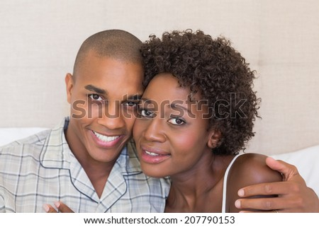 Happy couple sitting on bed cuddling at home in the bedroom - stock photo