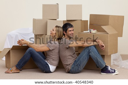 Happy couple sitting on floor unpacking boxes after moving house - stock photo