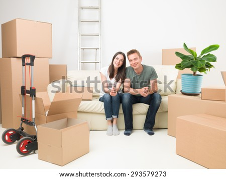 happy couple sitting on sofa after moving in new house - stock photo
