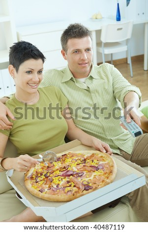 Happy couple sitting on sofa eating pizza and watching TV at home, smiling. - stock photo