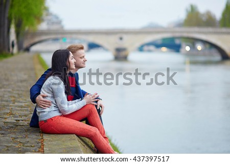 Happy couple sitting on the bank of the Seine in Paris. Tourists enjoying their vacation in France. Romantic date or traveling couple concept - stock photo