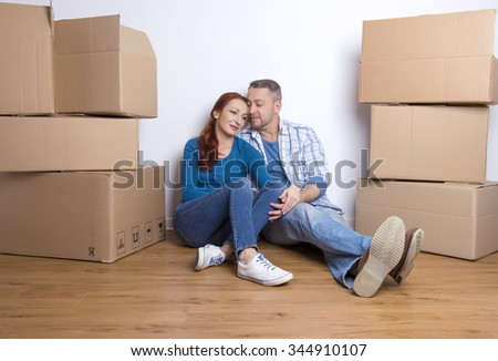 happy couple sitting on the floor in their new home with cardboard boxes - stock photo