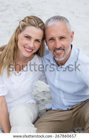 Happy couple sitting on the sand and looking at the camera at the beach - stock photo