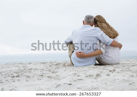 Happy couple sitting on the sand and looking at the sea at the beach - stock photo