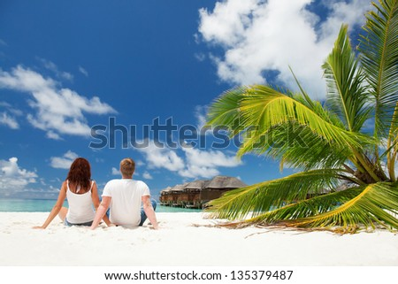 Happy couple sitting on the sunny beach - stock photo