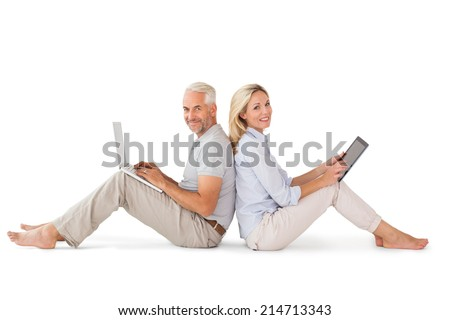 Happy couple sitting using laptop and tablet pc on white background - stock photo