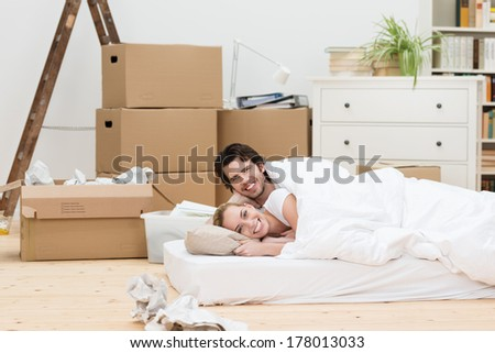 Happy couple sleeping on the floor in their new home lying on a mattress in the living room surrounded by cardboard boxes - stock photo