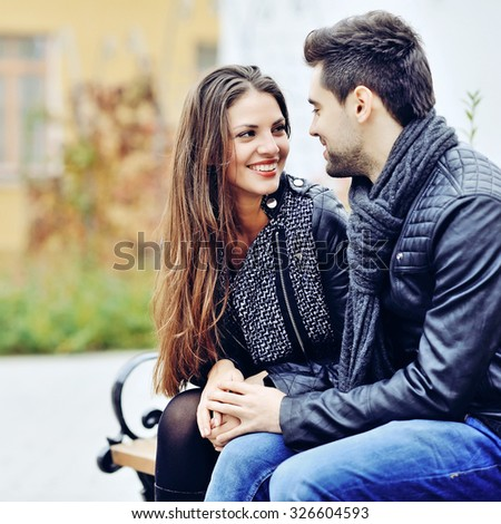 Happy couple smiling and looking each other outdoors  - stock photo