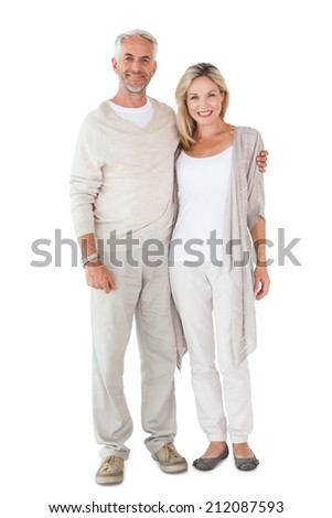 Happy couple smiling at camera together on white background - stock photo