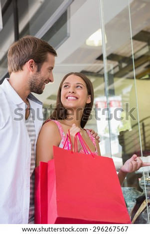 Happy couple smiling at each other in front of a clothing shop - stock photo