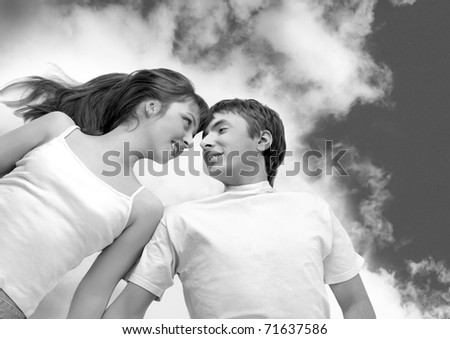 happy couple smiling  having fun,  lying on clouds - stock photo