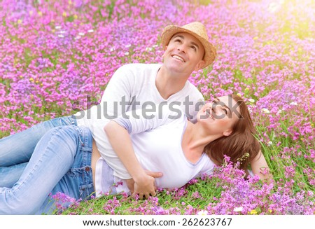 Happy couple spending time outdoors, lying down and hugging on beautiful pink flower field, romantic relationship, love and happiness concept - stock photo