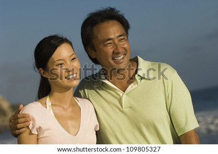Happy couple spending time together on the beach - stock photo