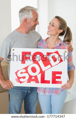 Happy couple standing and holding sold sign in their new home - stock photo