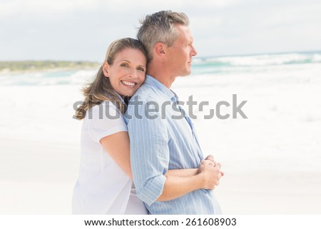 Happy couple standing and hugging at the beach - stock photo