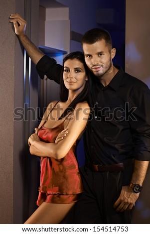 Happy couple standing at door, woman in sexy pyjamas, both smiling. - stock photo