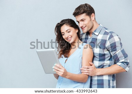Happy couple standing at home and using digital tablet isolated on gray background - stock photo