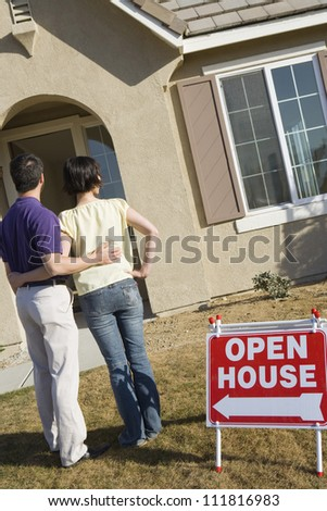 Happy couple standing in front of their new home - stock photo