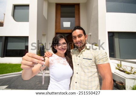 happy couple standing outdoors holding key to their new house - stock photo