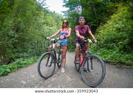 happy couple stays on a mountain road in the woods on bikes looking way - stock photo