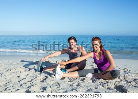 Happy couple stretching together beside the water at the beach - stock photo