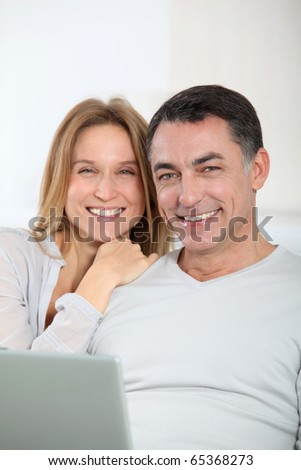 Happy couple surfing on internet at home - stock photo