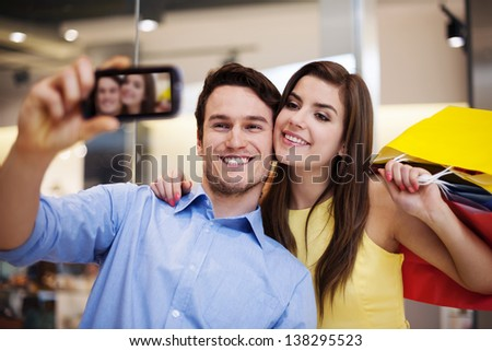 Happy couple taking a photo in the shopping mall - stock photo