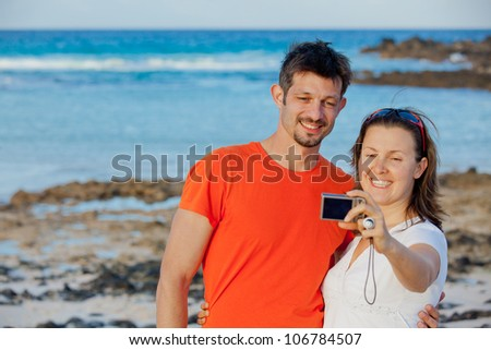 Happy couple taking a self portrait with a camera - stock photo
