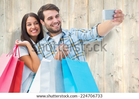 Happy couple taking a selfie against pale wooden planks - stock photo