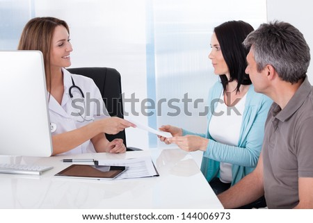 Happy Couple Taking Giving Card From Doctor - stock photo