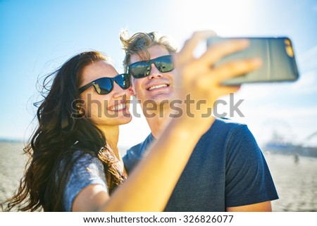 happy couple taking romantic selfie on beach with bright sun with lens flare and selective focus - stock photo