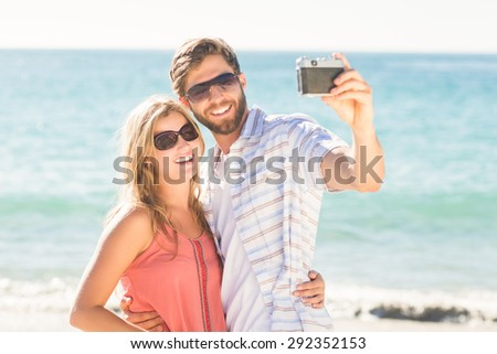 Happy couple taking selfie at the beach - stock photo
