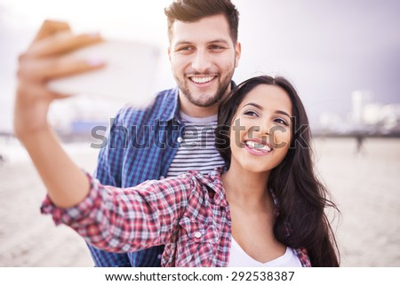 happy couple taking selfie on beach with smartphone - stock photo