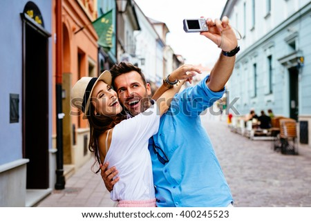 Happy couple taking selfie on the street during Europe vacation - stock photo